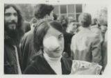 Woman with an eye bandage that reads, I was protected by the police, and Ian J. Grand in background, San Francisco...